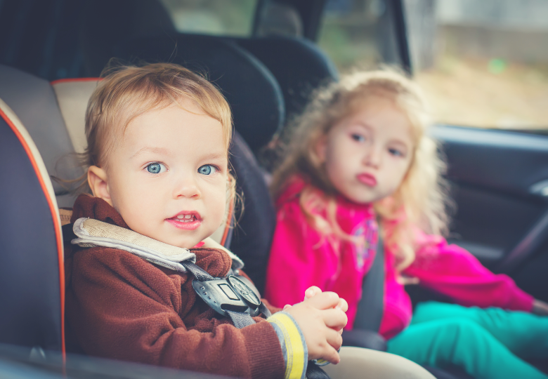 Two children in car seats in the back of a car