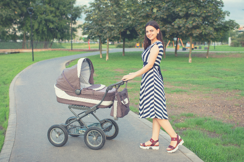 Mother and baby in bassinet-style pram in park
