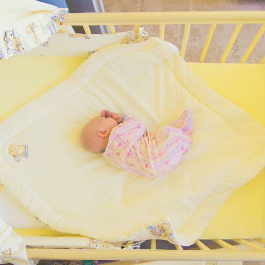 new born baby photographed from above in cot with yellow bedding
