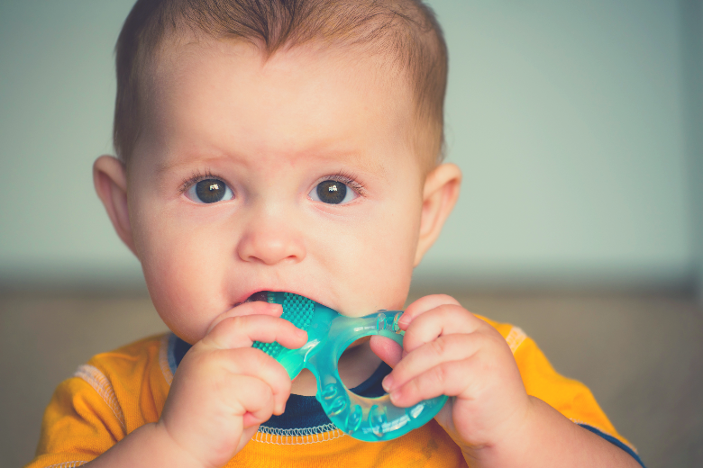 Baby boy with teether in his mouth