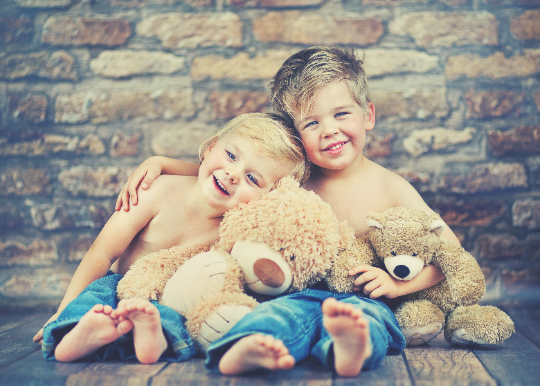 two toddler brothers and their teddy bears having a cuddle