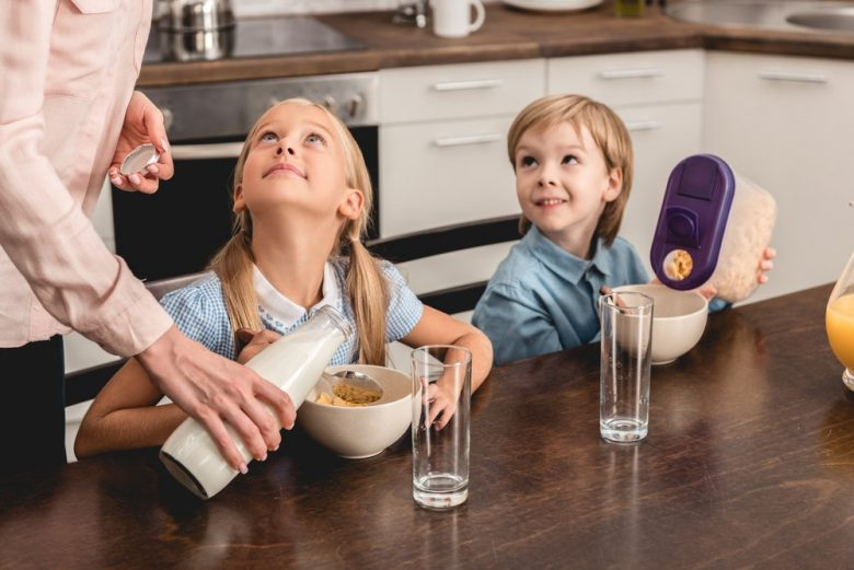 two happy children eating breakfast with mother pouring milk